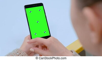 Woman touching blank green screen of black smartphone -...