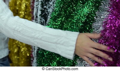 Woman touching Christmas tinsel in the store - Close-up shot...