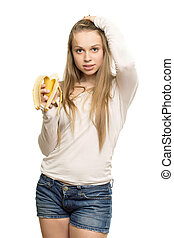 Woman touching her hair - Young pretty woman holding banana...