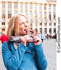 Woman tourist bites a bar of chocolate at the Grand Place in Brussels, Belgium