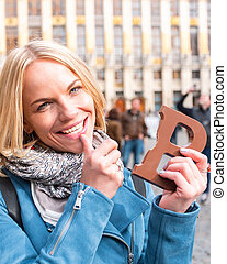 Woman tourist holding a bar of chocolate at the Grand Place in Brussels, Belgium