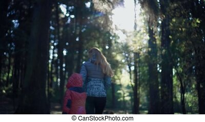 Woman tourist holds her daughter's hand in the woods and...