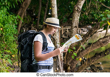 woman tourist in a hat with a backpack on a hike in Asia