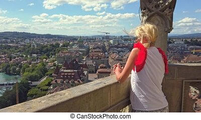 Woman tourist looking Bern old town, capital of Switzerland, and Aare River with bridges, from panoramic terrace of Bell Tower Cathedral. Aerial view of medieval cityscape UNESCO World Heritage site.