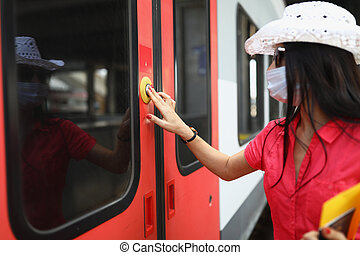 Woman tourist in protective medical mask pressing button to open train door