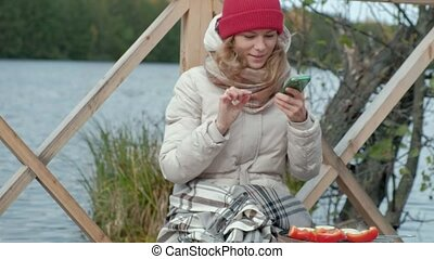 Woman tourist in warm clothes on the bridge by the river with a backpack, prepares vegetables on the grill, takes pictures of food on the phone, picnic, outdoor activities, healthy lifestyle. Travel concept