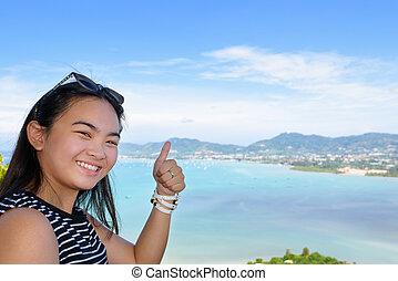 Woman tourist lifting thumb praise beautiful of sea in Phuket, Thailand