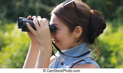 Woman tourist looking through binoculars closeup. - Girl...
