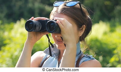 Woman tourist looking through binoculars closeup. Watch the...