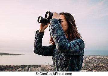 Woman tourist looking through binoculars on nature.