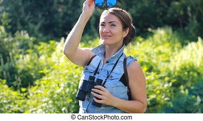 Woman tourist looking through binoculars