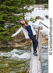 Woman tourist on a wooden bridge