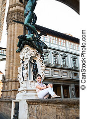Woman tourist sitting in Loggia dei Lanzi in Florence, Italy...