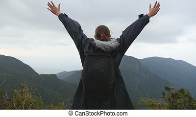 Woman tourist standing on the edge of beautiful canyon, victoriously outstretching arms up. Young female hiker with backpack reaching up top of mountain and raised hands. Slow motion Rear back view