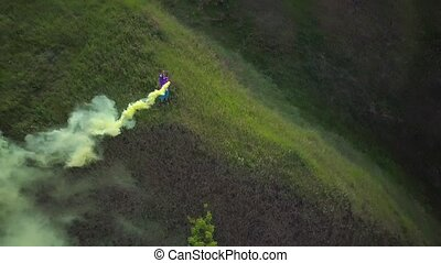 Woman tourist stands on top of a hill and waving with a smoke bomb
