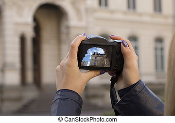 Woman tourist take picture of a beautiful old building