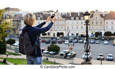 Woman tourist taking a photo of a city square