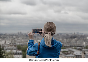 Woman tourist taking photo of the city in cloudy weather