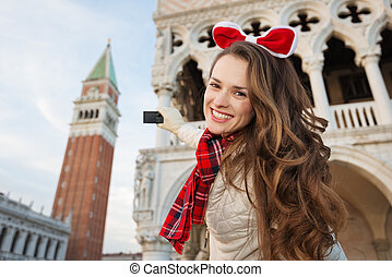 Woman tourist taking photos of Christmas Venice, Italy
