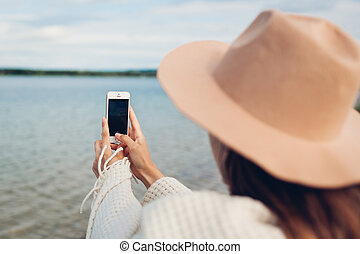 Woman tourist taking picture of autumn lake ladscape using smartphone. Traveler in hat covered with blanket takes photos