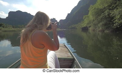 Woman tourist taking shots of Trang An nature, Vietnam