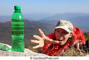 Woman tourist tries in the mountains reaches for a bottle of drinking water