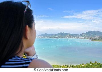 Woman tourist watching the ocean in Phuket, Thailand