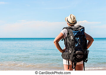 woman tourist with a backpack admiring the beautiful scenery of the sea