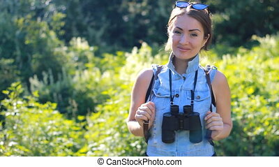 Woman tourist with a backpack and binoculars smiling before...