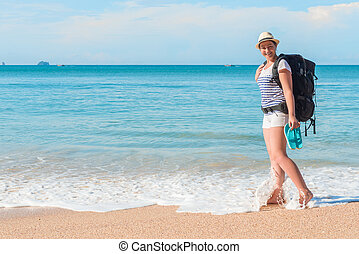 woman tourist with a backpack in the sea with bare feet