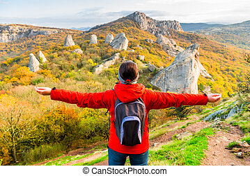 Woman Tourist with a backpack with open arms enjoying the autumn landscape in the mountains