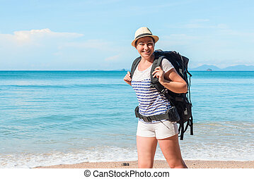 woman tourist with a big backpack on the background of a beautiful sea in Thailand in a hike