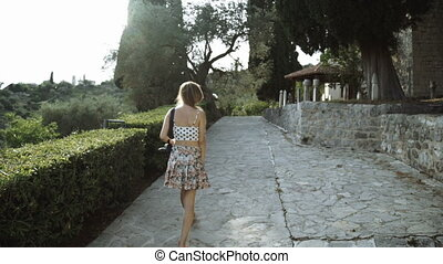 woman tourist with a camera walking. Beautiful view of whitewashed houses. Young female photographer is wearing sunhat during