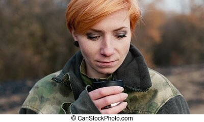 Woman tourist with a cup of tea on nature