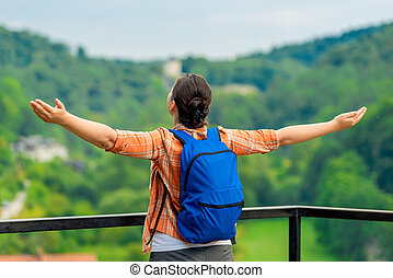 woman tourist with arms outstretched enjoys freedom in nature