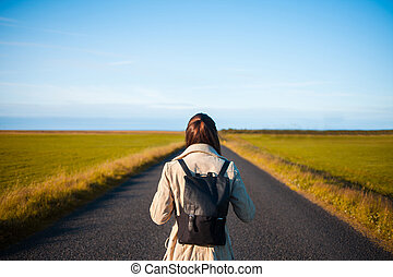 Woman tourist with backpack on the background road. Toward the goal