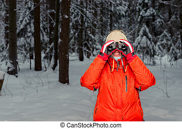 woman tourist with binoculars in the winter forest