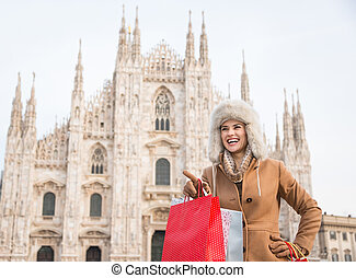 Woman tourist with shopping bags pointing on copy space in Milan