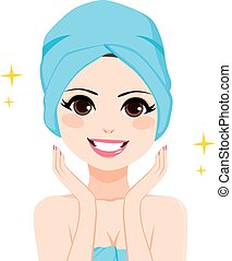 Woman with hair wrapped in blue bath towel showing perfect facial skin