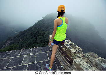 woman trail runner haves a rest at great wall on the top of mountain