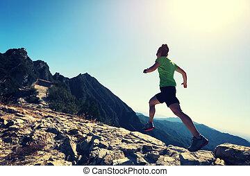 woman trail runner running at mountain top
