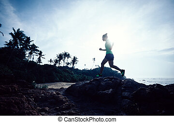 Woman trail runner running at rocky mountain top on seaside