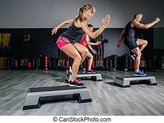Woman trainer doing aerobic class with steppers in gym -...