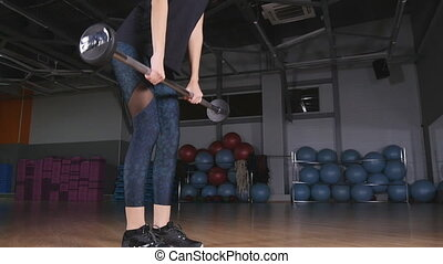 Woman training deadlift at gym
