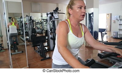 Woman Training On Exercise Bicycle