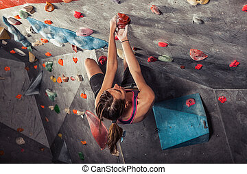 woman training on practice climbing wall indoor