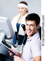 Woman training on simulators in gym with coach
