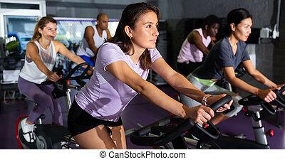 Woman training on stationary bike in gym