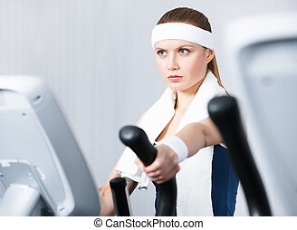 Woman training on training apparatus in gym