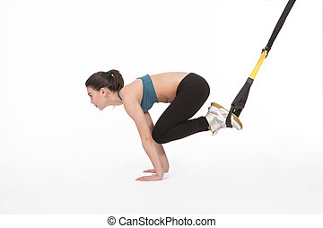 Woman training with suspension trainer sling